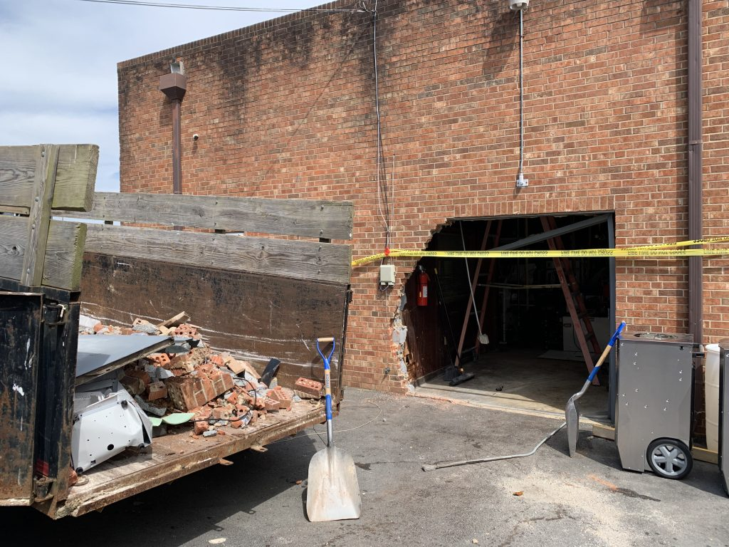 hole in brick wall by car